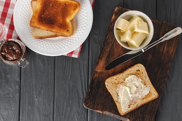 Простой завтрак. поджаренный хлеб с маслом на деревянном столе