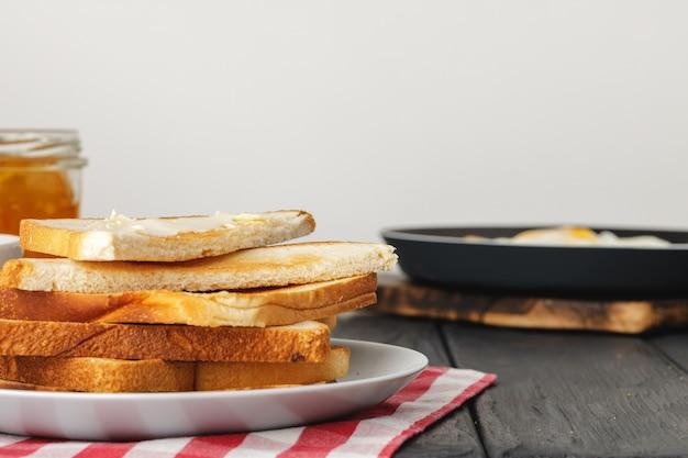 簡単な朝食。木製のテーブルの上にバターで覆われたトーストしたパン