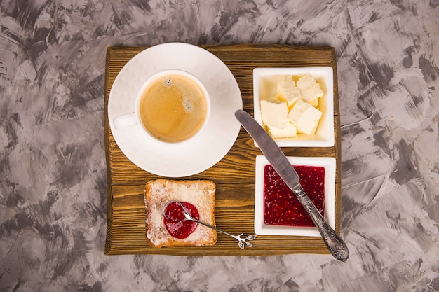 Simple breakfast of traditional products - toast with butter and raspberry jam