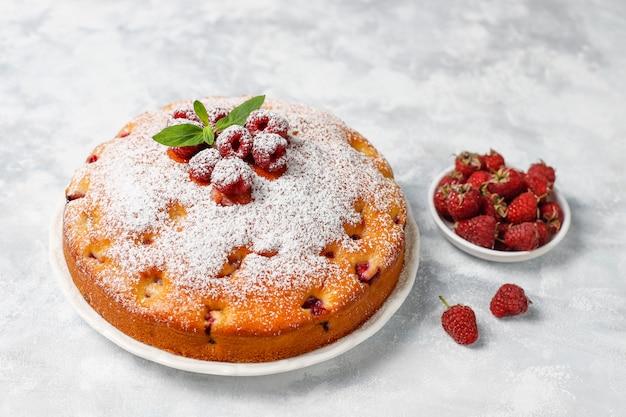 Простой пирог с сахарной пудрой и свежей малиной на свету. летний ягодный десерт.