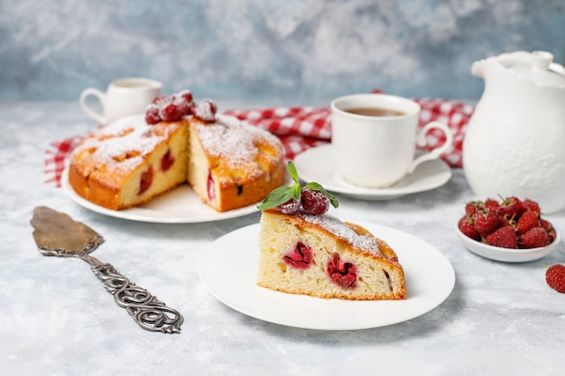 Simple cake with powdered sugar and fresh raspberries on a light . summer berry dessert.