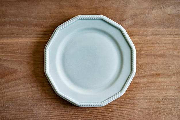 A simple ceramic plate placed on a wooden dining table