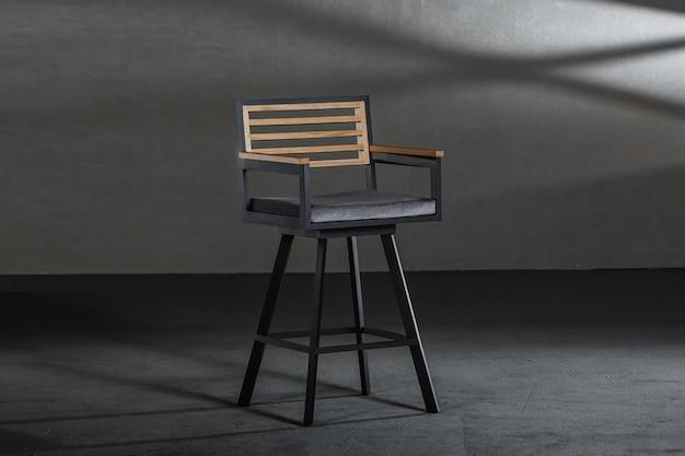 회색 벽이있는 방에 금속 높은 다리가있는 단순한 의자