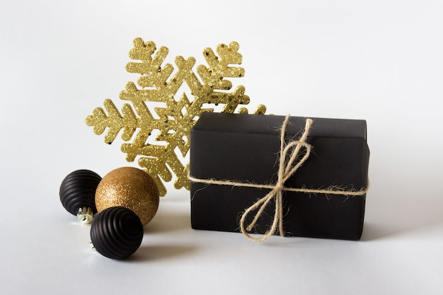 Simple christmas composition with a present wrapped in black paper and decorative baubles and golden snowflake on white surface
