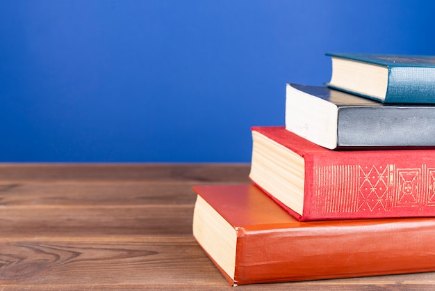 A simple composition of many hardback books, multi-colored books on a wooden table