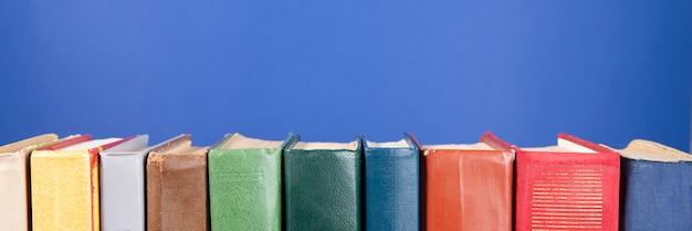 Простой состав книг в твердом переплете, сырые книги на синем фоне. стопка книг без надписей, пустой корешок. обратно в школу. открытая книга. место для текста.
