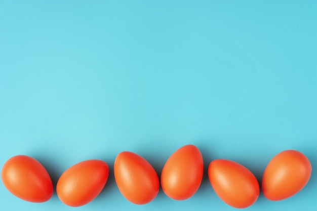 Simple composition with vivid orange easter eggs on blue-green background