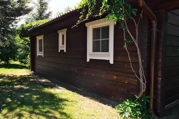 Простой коттедж из темного дерева в солнечный летний день. стена гостевого дома с тремя окнами. праздники, выходные, отдых на природе.