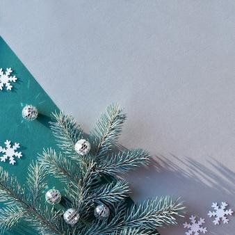 コピースペースとシンプルな装飾的な冬の背景。緑と灰色のツートンカラーの紙にモミの小枝。