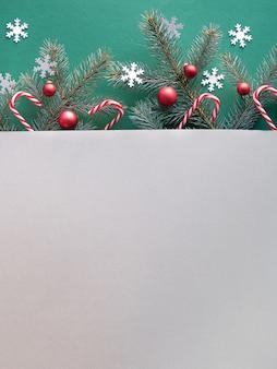 テキストスペースとシンプルな装飾的な冬の背景。緑と灰色のツートンカラーの紙にモミの小枝。