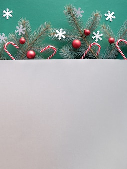 Simple decorative winter background with text space. fir twigs on two tone green and grey paper.