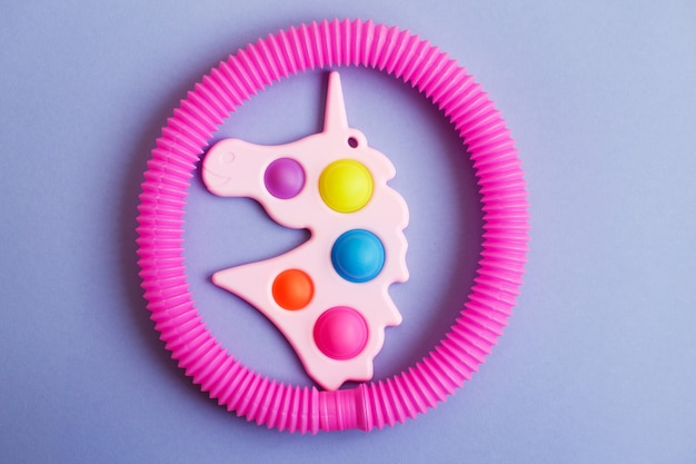 ユニコーンの形のシンプルなディンプルと紫色の背景にチューブのそわそわおもちゃ