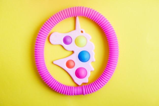 노란색 배경에 유니콘 형태의 단순한 보조개와 튜브 피젯 장난감