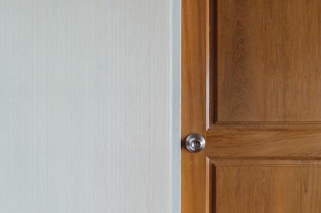 Simple door knob of a wooden door with empty wall.