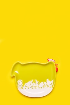 노란색 위에 녹색 암탉 접시와 간단한 부활절 배경