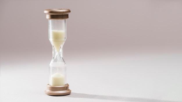 Simple and elegant sand-glass timer against colored background