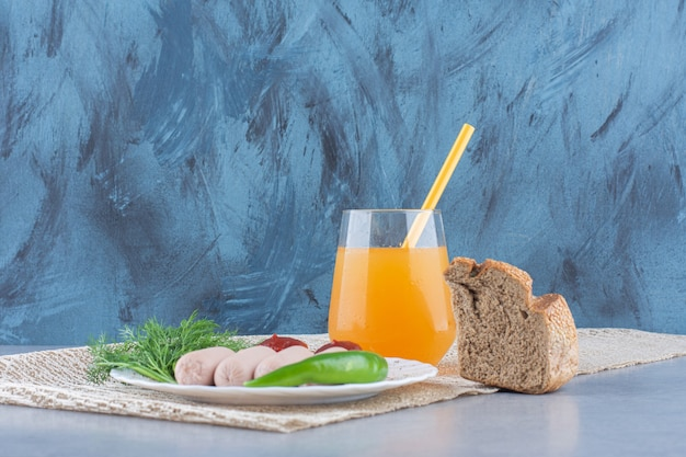 シンプルなイングリッシュブレックファースト。ソーセージとオレンジジュースとパン。