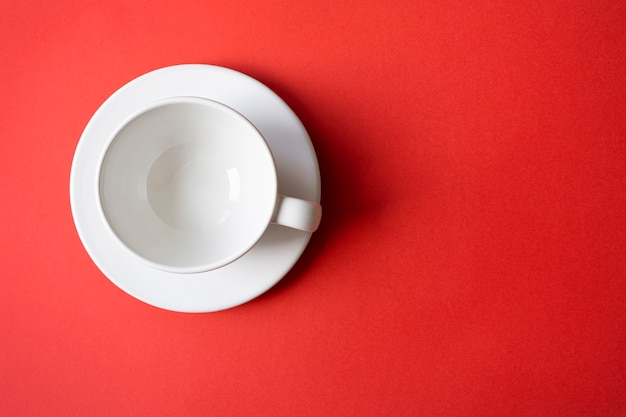 Simple flat lay composition with empty white ceramic cup mug bowl on a plate