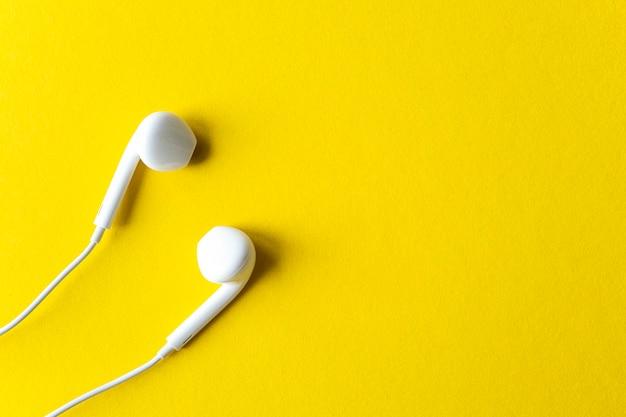 明るい黄色の背景に白いヘッドフォンでシンプルなフラットレイ構成