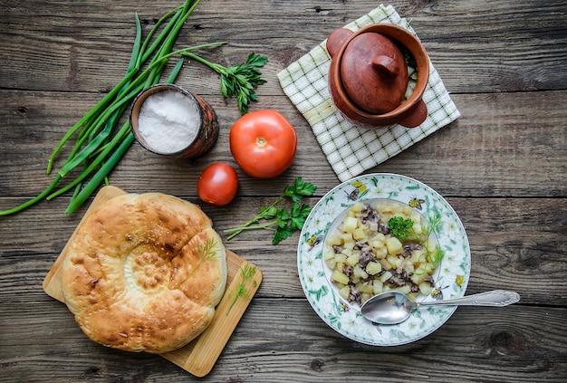 간단한 음식 : 뜨거운 고기와 감자가 든 냄비, 붉은 익은 토마토, 식욕을 돋우는 둥근 케이크, 채소, 소박한 나무 표면에 소금