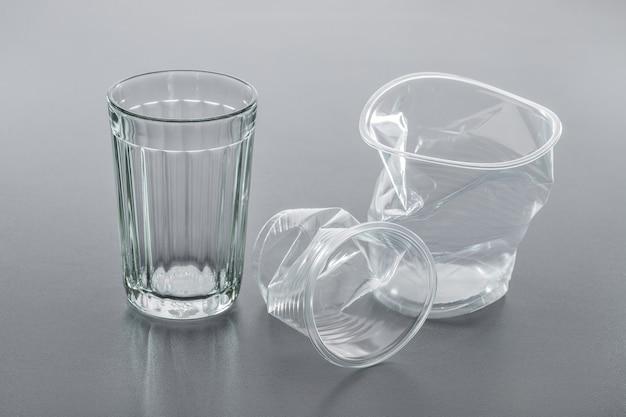 灰色の背景、クローズアップのシンプルなガラスとしわくちゃのプラスチックカップ。リサイクルの概念。