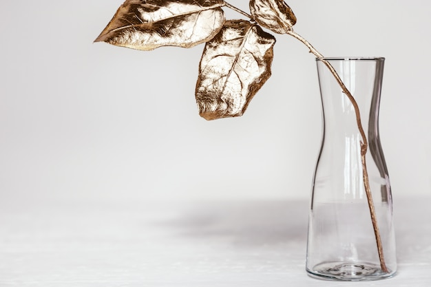 Simple glass vase with branch of tree and bright gold colored leaves on white table. modern home decoration plant.