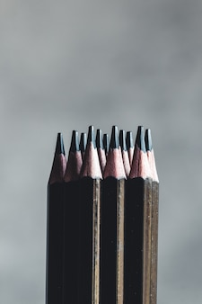 Simple graphite pencils on grey background. black pencils, space for text