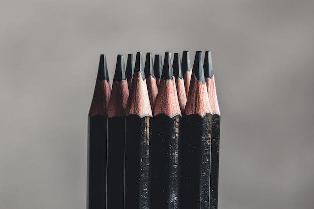 회색 배경에 간단한 흑연 연필입니다. 검은 연필, 텍스트를위한 공간