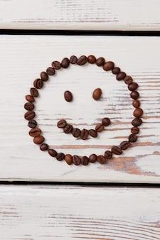 コーヒー豆で作った素朴な幸せな笑顔。白い木の板の上に横たわるスマイリーの形に配置されたロースト コーヒーの粒。