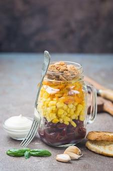 とうもろこし、玉ねぎ、豆、にんじん、クルトン、マヨネーズを添えたシンプルな自家製メイソンジャーサラダ Premium写真