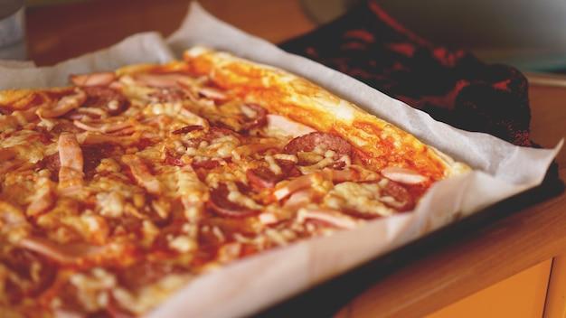 Простая домашняя пицца на деревенском деревянном столе.