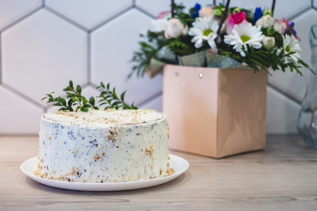 Simple homemade white cake with nuts on kitchen countertop on background of bouquet of different flowers in paper bag with handles