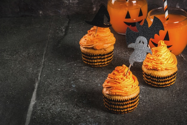 Простая идея забавного детского угощения для хэллоуина: тыквенные пирожные с кремом с украшениями в виде праздничных символов - летучая мышь-призрак на черном фоне