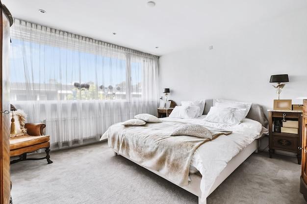 햇빛 아래 창문과 안락 의자 근처에 쿠션과 격자 무늬가있는 퀸 사이즈 침대가있는 현대 침실의 심플한 인테리어