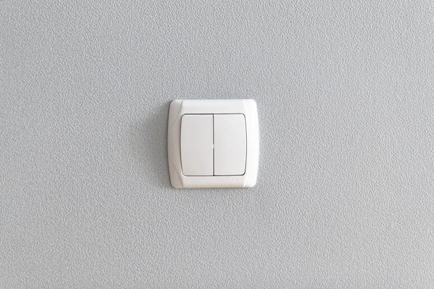 Simple light switch on grey wall.