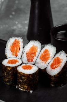 Простые маки со свежим лососем. суши на сером фоне.