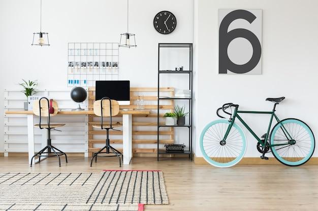 木製の机とオフィスチェアの隣に立っているレトロなアクセサリーとシンプルな金属ラック