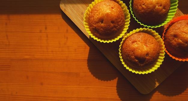 Простые мини-кексы в разноцветных силиконовых формах для выпечки. свободное место. крупный план. концепция кухни и приготовления пищи на деревянных фоне