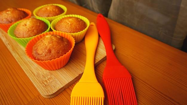 컬러풀한 실리콘 베이커리에 담긴 심플한 미니 머핀. 실리콘 컵 베이킹 컵 케이크와 실리콘 브러시. 나무 배경에 부엌과 요리 개념