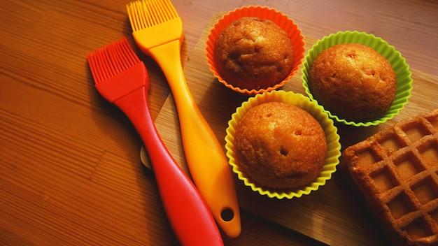 Простые мини-кексы в разноцветных силиконовых формах для выпечки. силиконовые чашки для выпечки кексов и силиконовые кисти. концепция кухни и приготовления пищи на деревянных фоне