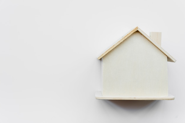 Simple miniature wooden house against white background