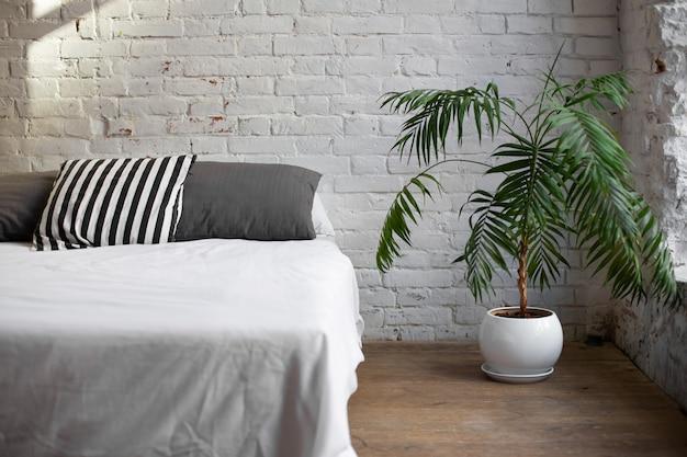 Простой современный интерьер спальни с живым цветком возле кровати