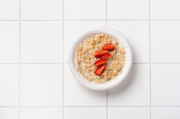 リネンナプキンの白いプレートにイチゴが入ったシンプルなオートミールのお粥。朝食健康食品のコンセプト。上面図。