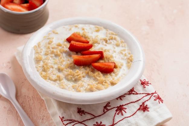 ピンクのリネンナプキンの白いプレートにイチゴが入ったシンプルなオートミールのお粥。朝食健康食品の概念