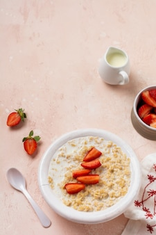 Simple oatmeal porridge with strawberries in a white plate on a linen napkin on pink. breakfast health food concept.