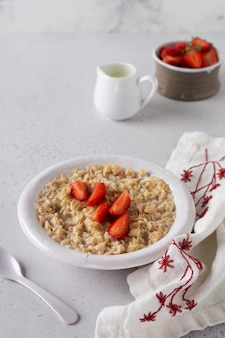 Simple oatmeal porridge with strawberries in a white plate on a linen napkin.