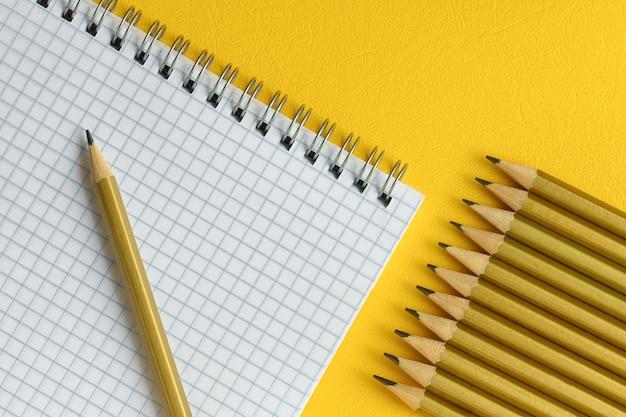 간단한 연필과 새장에 노트북을 닫습니다, 노란색 배경