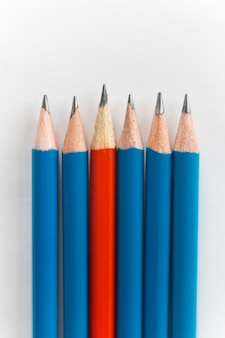Simple pencils, one red among the blue