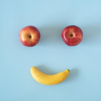 青い背景に配置されたリンゴの桃とバナナで作られたシンプルな丸いフルーツのページ