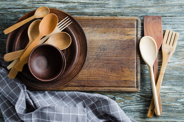 Simple rustic kitchenware against vintage wooden background.